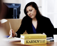 Prosecutor at table with two Karnov law books